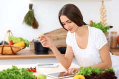 Beautiful Hispanic  woman is making online shopping by tablet computer and credit card or searching internet for a ne Royalty Free Stock Photography