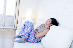 Beautiful hispanic woman in painful expression holding belly suffering menstrual period pain. Young beautiful hispanic woman in painful expression holding her royalty free stock images