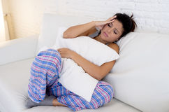 Beautiful hispanic woman in painful expression holding belly suffering menstrual period pain. Young beautiful hispanic woman in painful expression holding pillow stock photography
