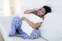 Beautiful hispanic woman in painful expression holding belly suffering menstrual period pain Stock Photos