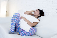 Beautiful hispanic woman in painful expression holding belly suffering menstrual period pain. Young beautiful hispanic woman in painful expression holding pillow royalty free stock photos