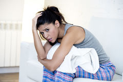 Beautiful hispanic woman in painful expression holding belly suffering menstrual period pain. Young beautiful hispanic woman in painful expression holding pillow Stock Image