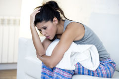 Beautiful hispanic woman in painful expression holding belly suffering menstrual period pain. Young beautiful hispanic woman in painful expression holding pillow Stock Photo
