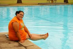 Beautiful Hispanic Woman by the pool. Young, beautiful Hispanic woman sitting by the pool Stock Photography