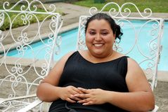 Beautiful Hispanic Woman by the pool. Young, beautiful Hispanic woman sitting by the pool Royalty Free Stock Photo