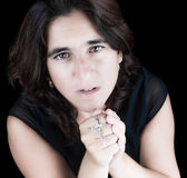 Beautiful hispanic woman praying Stock Photo