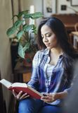 Beautiful hispanic woman reading a paper book. Portrait of beautiful hispanic woman reading a paper book at home stock image
