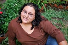 Beautiful Hispanic woman sitting. On the grass Royalty Free Stock Photo