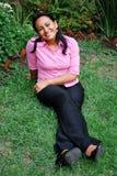 Beautiful Hispanic woman sitting. On the grass Royalty Free Stock Photos