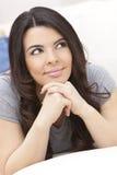 Beautiful Hispanic Woman on Sofa Smiling Stock Photography
