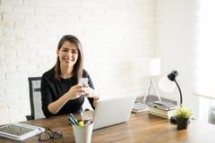 Latin woman texting at work Stock Photography
