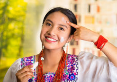 Beautiful hispanic woman wearing white blouse with colorful embroidery, applying cream onto face using finger during Stock Image