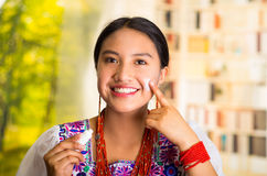 Beautiful hispanic woman wearing white blouse with colorful embroidery, applying cream onto face using finger during Stock Images