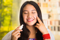 Beautiful hispanic woman wearing white blouse with colorful embroidery, applying cream onto face using finger during Royalty Free Stock Photo