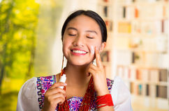 Beautiful hispanic woman wearing white blouse with colorful embroidery, applying cream onto face using finger during Royalty Free Stock Photos
