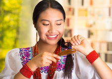 Beautiful hispanic woman wearing white blouse with colorful embroidery, using small hairbrush during makeup routine. Garden background Stock Photos