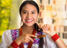 Beautiful hispanic woman wearing white blouse with colorful embroidery, using small hairbrush during makeup routine. Garden background Stock Photography