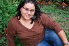 Beautiful Hispanic women sitting outside. A beautiful Hispanic student sitting outside on a college campus Stock Photos