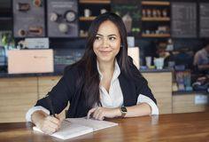 Beautiful hispanic young woman in suit working in the cafe royalty free stock photo