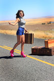 Curvy Hitch Hiker. A curvy sexy brunette beauty wearing short shorts and pink high heel boots is hitch hiking with her luggage on a remote desolate country road Royalty Free Stock Photos