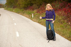 Beautiful hitchhiker on autumn road Royalty Free Stock Images