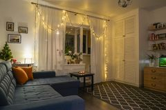 Beautiful holdiay decorated room. With small Christmas tree, table lamp and blue comfortable couch with cushions on it. All photos in photo frames in this Stock Image