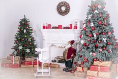 Beautiful holdiay decorated room with Christmas tree with presents under it. Children`s swing, Santa, candles. white vignette Royalty Free Stock Images