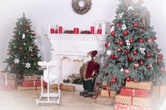 Beautiful holdiay decorated room with Christmas tree with presents under it. Children`s swing, Santa, candles. white vignette Stock Photos