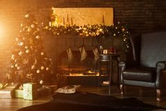 Beautiful holdiay decorated room with Christmas tree. With presents under it. Beautiful fireplace, candles, lights and chair in the room stock photography