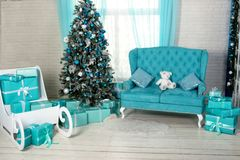 Beautiful holdiay decorated room with Christmas tree with presents under it. light blue, turquoise and white interior shades with Royalty Free Stock Images