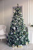 Beautiful holdiay decorated room with Christmas tree. Christmas tree in the room in the snow, decorated with toys and lay next to the gifts in boxes Stock Photo