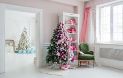 Beautiful holdiay decorated rooms with Christmas trees, shelf and pink blue gifts on it, green chair home interior Royalty Free Stock Photography