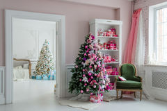 Beautiful holdiay decorated rooms with Christmas trees, shelf and pink blue gifts on it, green chair home interior Stock Photo