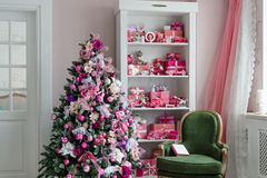 Beautiful holdiay decorated rooms with Christmas trees, shelf and pink blue gifts on it, green chair home interior Stock Photos
