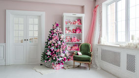 Beautiful holdiay decorated rooms with Christmas trees, shelf and pink blue gifts on it, green chair home interior Royalty Free Stock Photos