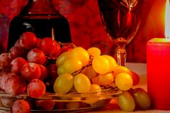 Beautiful holiday composition with wine, grape and candle stock image
