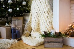 Beautiful holiday cozy room with Christmas tree, fireplace and white blanket Royalty Free Stock Image