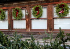 Beautiful holiday wreaths and fir branches on wood building Royalty Free Stock Photos
