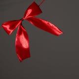 Beautiful holidays red satin bow on gray Royalty Free Stock Photos