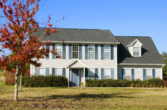 Beautiful home. With a fall red leaf maple tree and blue sky Stock Photos