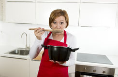 Beautiful home cook woman at kitchen holding spoon and cooking pot tasting delicious soup Stock Photography