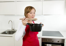 Beautiful home cook woman at kitchen holding spoon and cooking pot tasting delicious soup Royalty Free Stock Photo