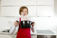 Beautiful home cook woman at kitchen holding spoon and cooking pot Stock Photo