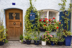 Beautiful home entrance with wooden door and flowers Royalty Free Stock Images