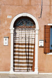 Beautiful home facade with door and striped curtains in Burano island (Venice, Italy) Royalty Free Stock Images