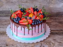 Beautiful home made cake with pink and turquoise cream cheese frosting. Decorated with strawberries and blueberries in a chocolate glaze stock photography