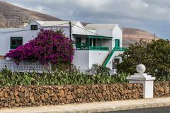 Beautiful home on the road. By walls surrounded the white house with Bougainvilleas Stock Photo