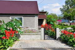 Beautiful home in the summer, decorated with red flowers Royalty Free Stock Image