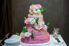 A beautiful home wedding four-tiered cake decorated with pink roses and leaves in a rustic style Royalty Free Stock Photos