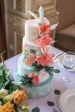 Home wedding for-tiered cake on the table in the restaurant decorated with pink roses and green leaves in a rustic style. A beautiful home wedding for-tiered stock photos